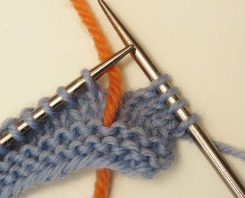 4. Leg de draad tussen twee steken naar achter.